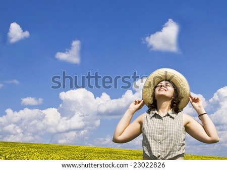 Young happy woman looking at heart shaped clouds - stock photo