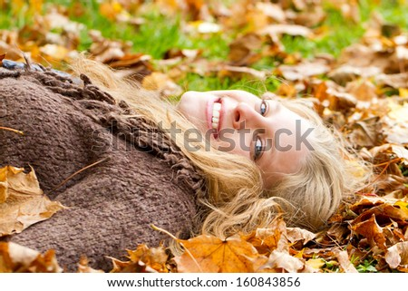 Young happy woman lying in autumn leaves