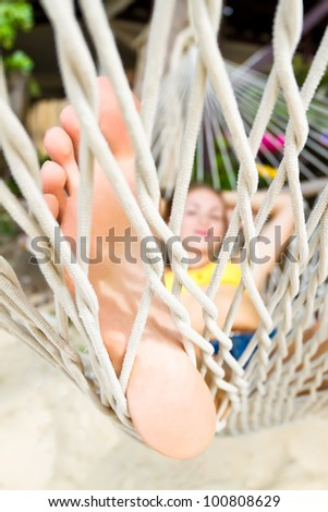 Young happy woman lying on a hammock at the beach