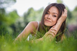 Young happy woman lying on grass in park. Close up Portrait