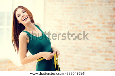 Young happy woman measuring her waist with a tape measure, at home, indoors. Caucasian model in healthy lifestyle, diet and  beauty concept shoot. Blank copyspace area for slogan or text message. #553049365