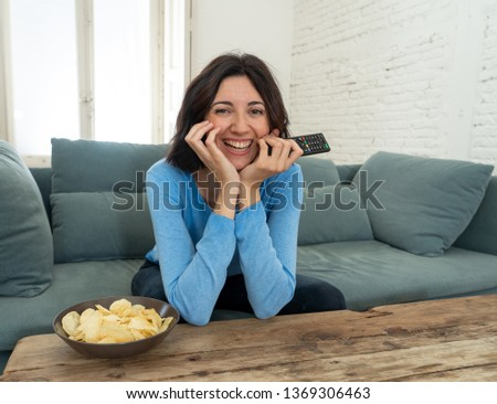 Young happy woman on sofa using TV remote control zapping for another movie or live sport. Looking enthusiastic, making gestures of approval and eating chips. In people, technology and leisure.