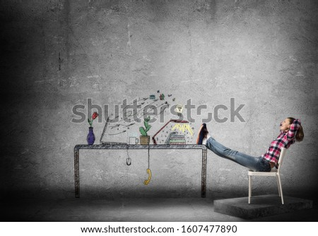 Young happy woman relaxing in room. Creative freelance designer sitting on chair and putting feets on table. Home workspace with computer on desk illustration on cancer wall. Relaxed workday