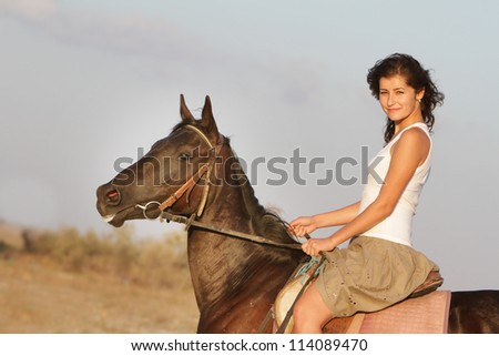 young happy woman riding horse on natural background
