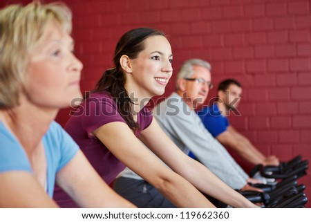 Young happy woman riding spinning bike in a fitness center