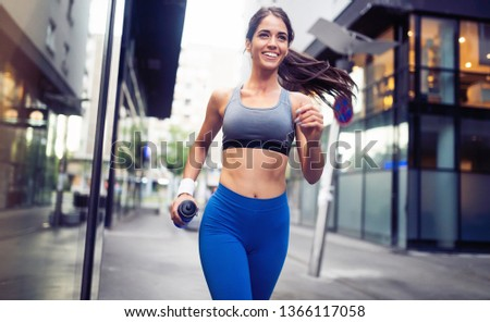 Young happy woman runner jogging in city outdoor