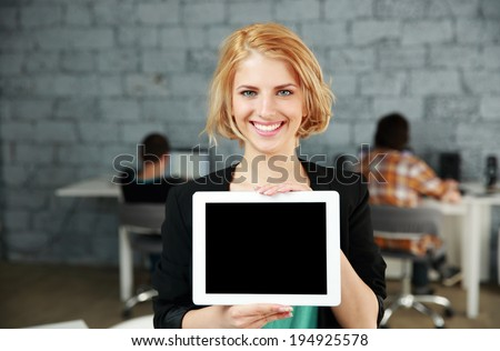 Young happy woman showing blank tablet computer screen in office