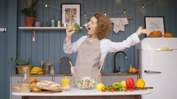 Young Happy Woman Singing And Dancing On Kitchen While Cooking Healthy Food.