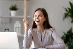 Young happy woman sitting at desk near laptop gesturing with hand make finger up, feels excited with good idea reach inspiration motivation, found solution for success at work or study, eureka concept