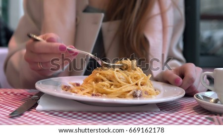 Stock Photo Young happy woman sitting at the table in cafe and enjoying the meal. Hungry woman eating tasty pasta.