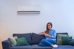 Young happy woman sitting on couch under air conditioner and adjusting comfort temperature with remote control at modern home