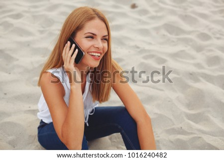 Young happy woman sitting on the beach sand and talking on the phone #1016240482