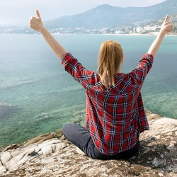 Young happy woman sitting on the edge and observing beautiful nature landscape with calm sea and island at background