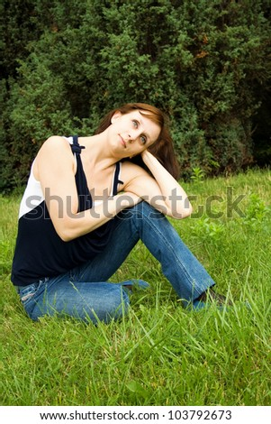 Young happy woman sitting on the green grass