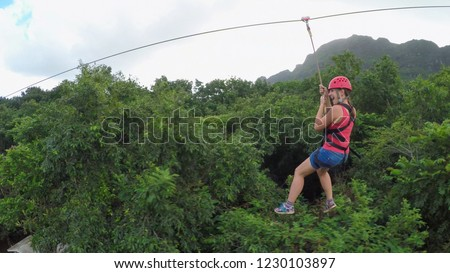 Young happy woman sliding on high speed zipline rope above beautiful tropic deciduous forest. Adrenaline gravity traveling from the top of the hill with overgrown jungle mountain in the background