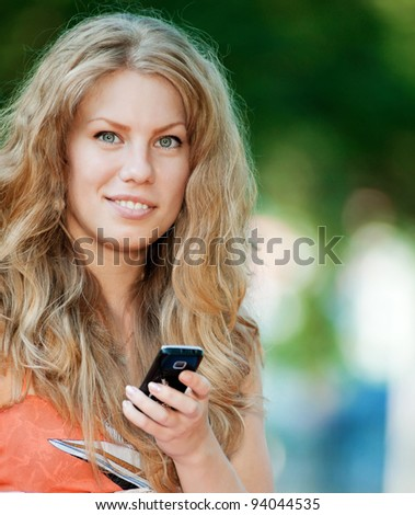 Young happy woman texting on mobile phone. SMS