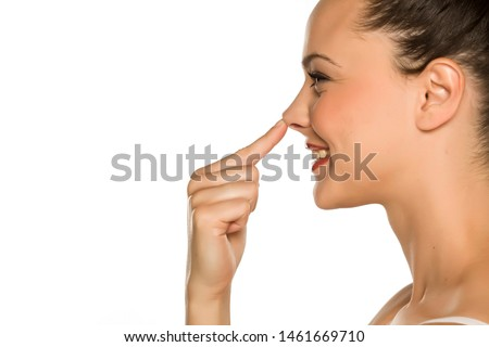 young happy woman touches her nose with her finger on a white background Photo stock ©