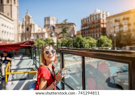 Young happy woman tourist in red dress having excursion in the open touristic bus in Valencia city, Spain #741294811