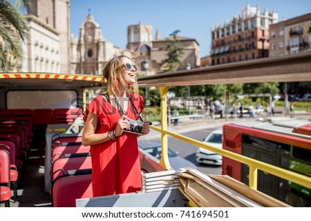 Young happy woman tourist in red dress having excursion in the open touristic bus in Valencia city, Spain #741694501