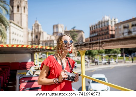 Young happy woman tourist in red dress having excursion in the open touristic bus in Valencia city, Spain #741694573