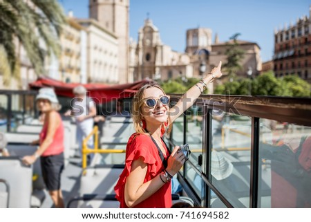 Young happy woman tourist in red dress having excursion in the open touristic bus in Valencia city, Spain #741694582