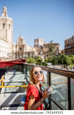 Young happy woman tourist in red dress having excursion in the open touristic bus in Valencia city, Spain #741694591