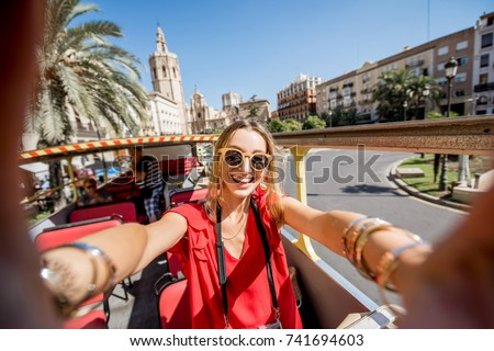 Young happy woman tourist in red dress having excursion in the open touristic bus in Valencia city, Spain #741694603