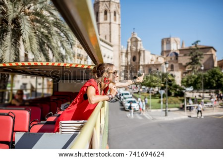 Young happy woman tourist in red dress having excursion in the open touristic bus in Valencia city, Spain #741694624