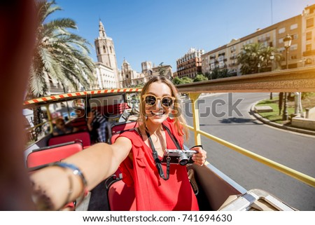 Young happy woman tourist in red dress having excursion in the open touristic bus in Valencia city, Spain #741694630