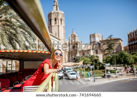 Young happy woman tourist in red dress having excursion in the open touristic bus in Valencia city, Spain #741694660
