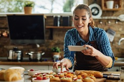 Young happy woman using smart phone and photographing food she has prepared in the kitchen.