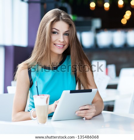 young happy woman using tablet computer in a cafe #135486068