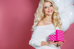 Young happy woman with a gift. Happy birthday. Sweet blonde woman holding small gift box with ribbon. Soft colors. Studio portrait over pink background.