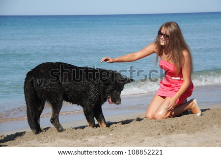 young happy woman with big black dog on beach