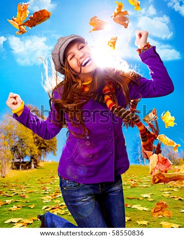 young happy woman with foliage in autumn