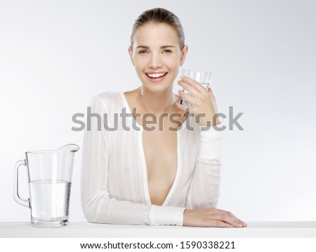 Young happy woman with glass of water, portrait