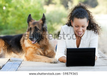 Young happy woman with her dog and laptop