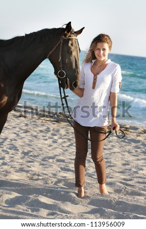 young happy woman with horse on sea background
