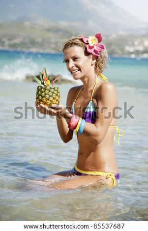young happy woman with pineapple cocktail in exotic destination