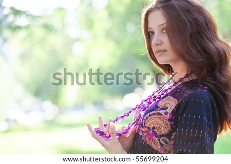 Young happy woman with purple beads at the summer park