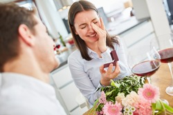 Young happy woman with wedding ring at marriage proposal at home wipes tear for joy from eyes