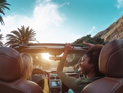 Young happy women doing a road trip in tropical city - Travel people having fun driving in trendy convertible car discovering new places - Friendship and youth girlfriends vacation lifestyle concept