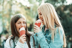Young happy women is having fun and eating ice cream.