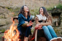 young happy women laughing, holding glass of red wine. Females warming next to the fire. Campfire, outdoors activities concept.