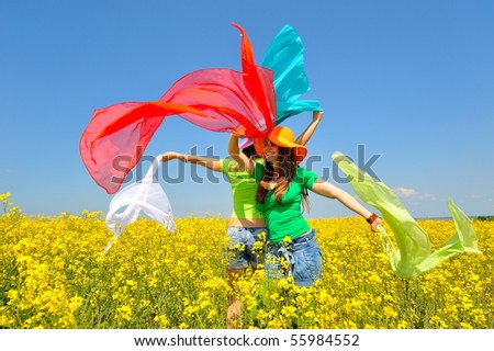 young happy women on blooming rapeseed field in summer
