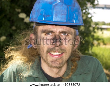 Young happy worker in green uniform and blue helmet