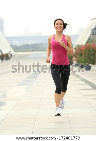 young healthy asian woman jogging at city in the morning - stock photo