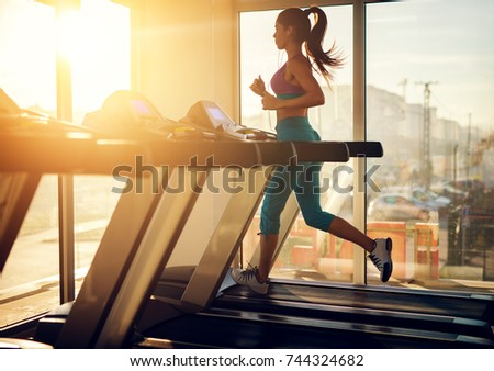 Young healthy athletic woman running on a treadmill near the sunny window in the gym and listening music.