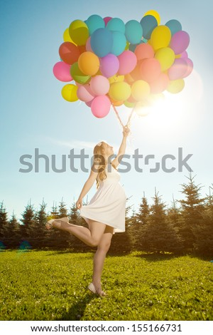 Young healthy beautiful pregnant woman with balloons outdoors. A girl with a tummy on the grass. Enjoyed by nature.