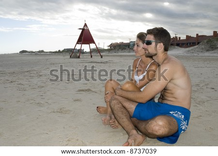Young healthy couple sited in the sand, looking out into the sea (side shot).